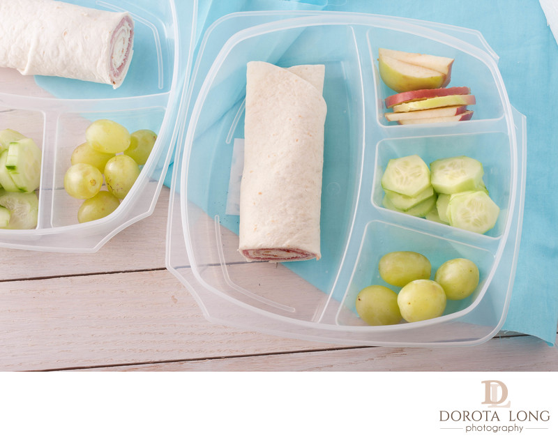 lunch box consisting of a wrap with ham and cheese, apples, grapes and sliced cucumber