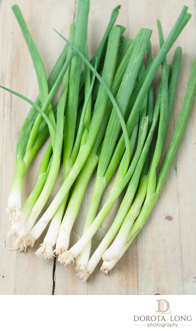 green onions isolated on wooden background