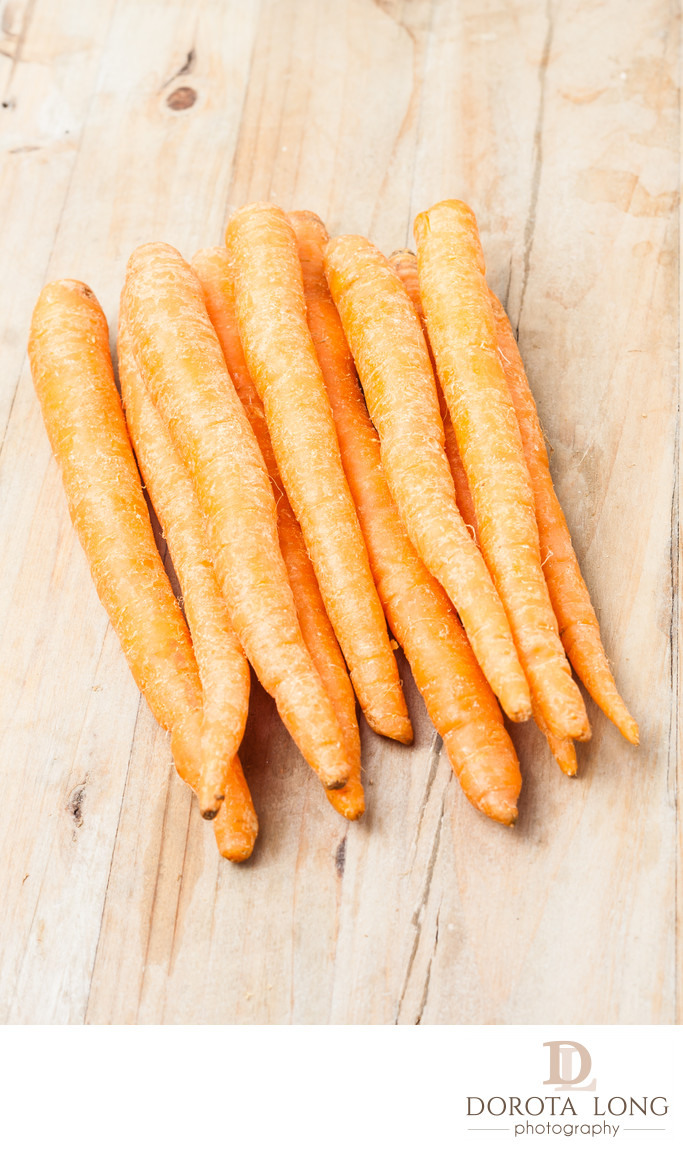 a bunch of fresh picked carrots on wooden background