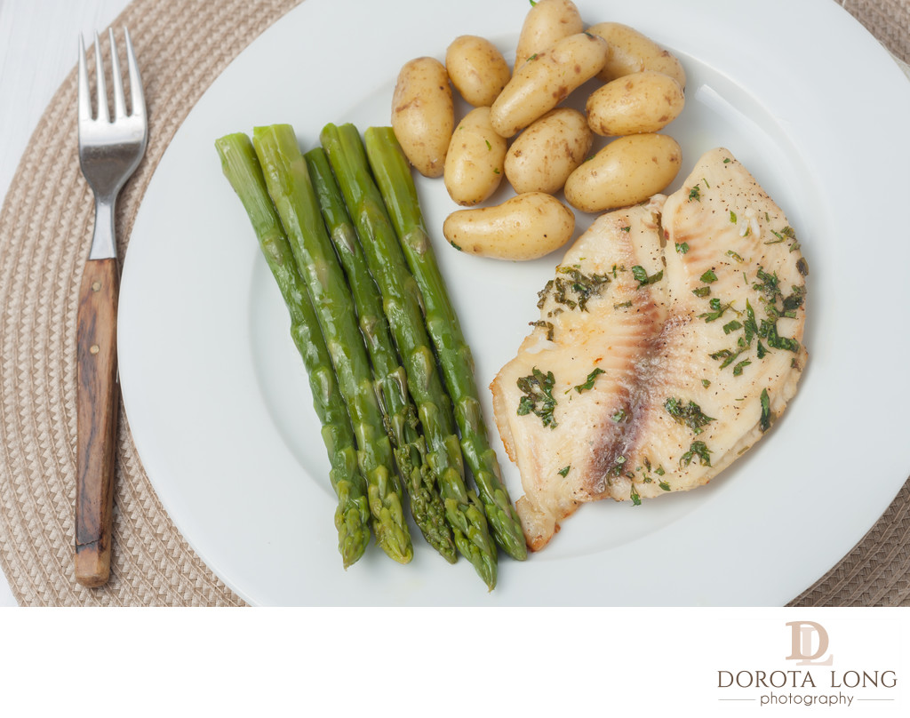 cooked fish with parsley servied with asparagus and baby potatoes on white plate