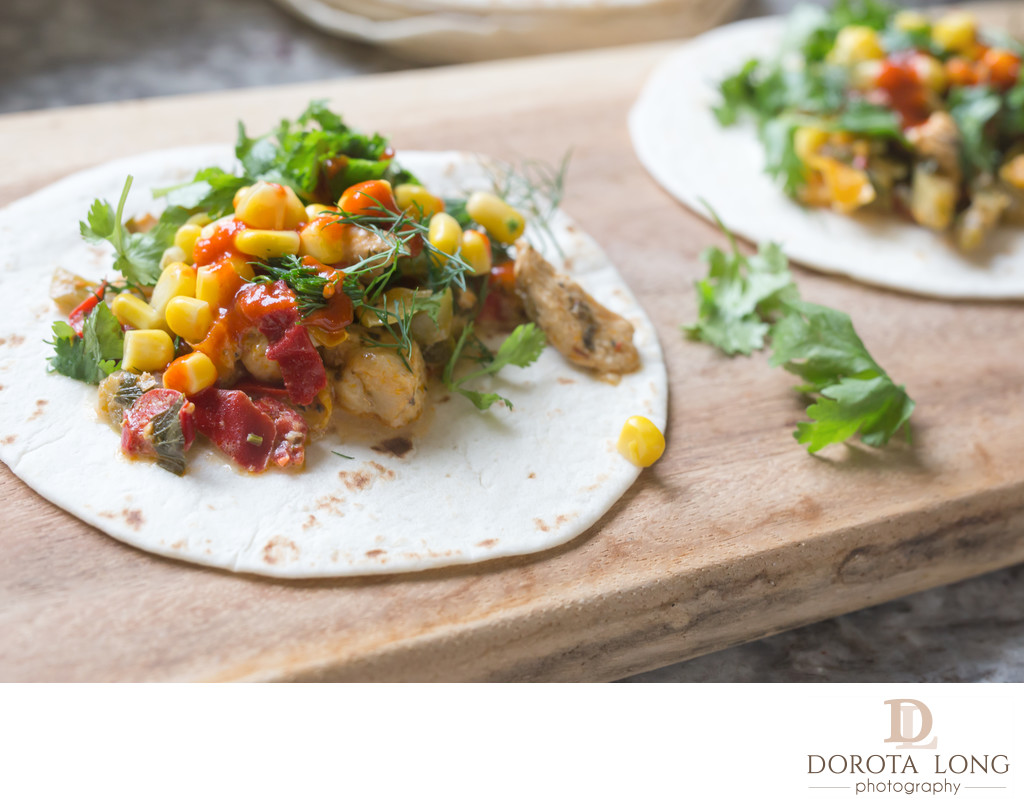 fresh tacos with chicken, vegetables and herbs on a wooden board