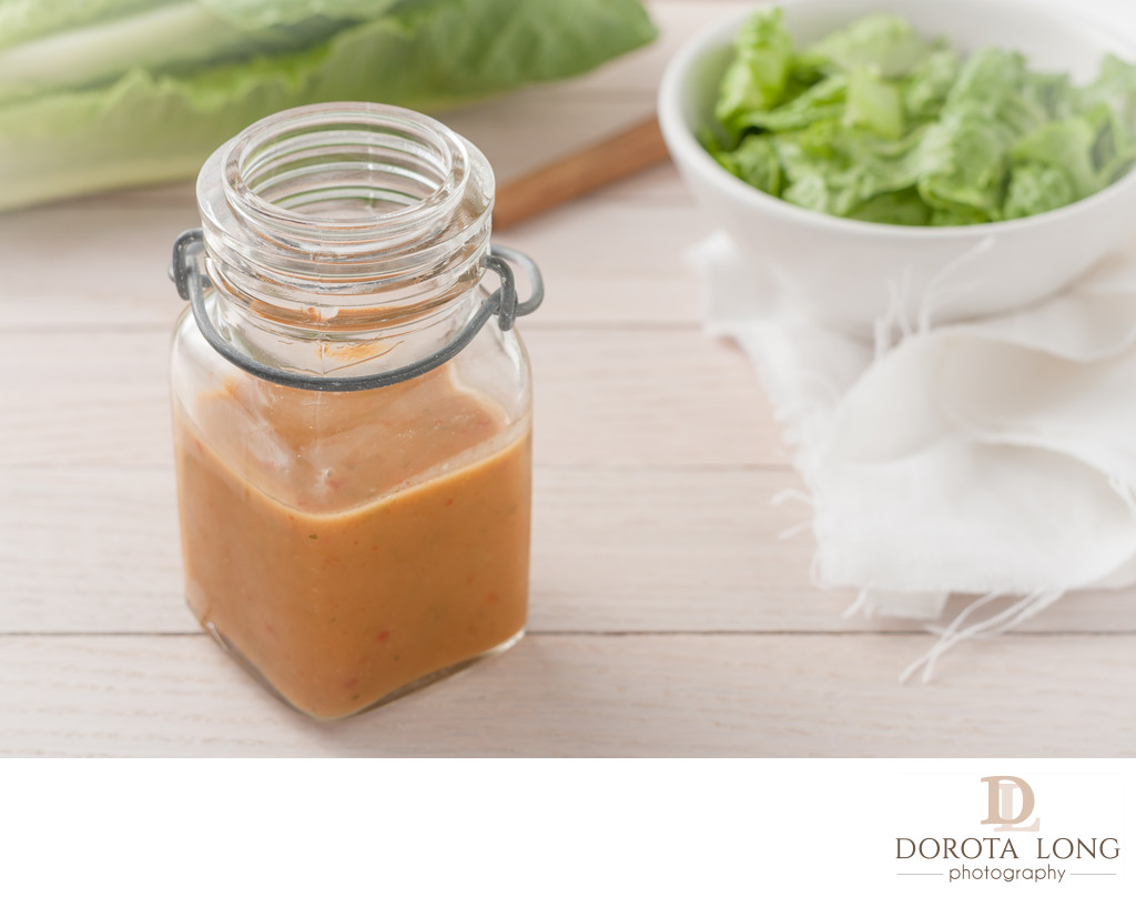 salad dressing in a glass container on light wooden background