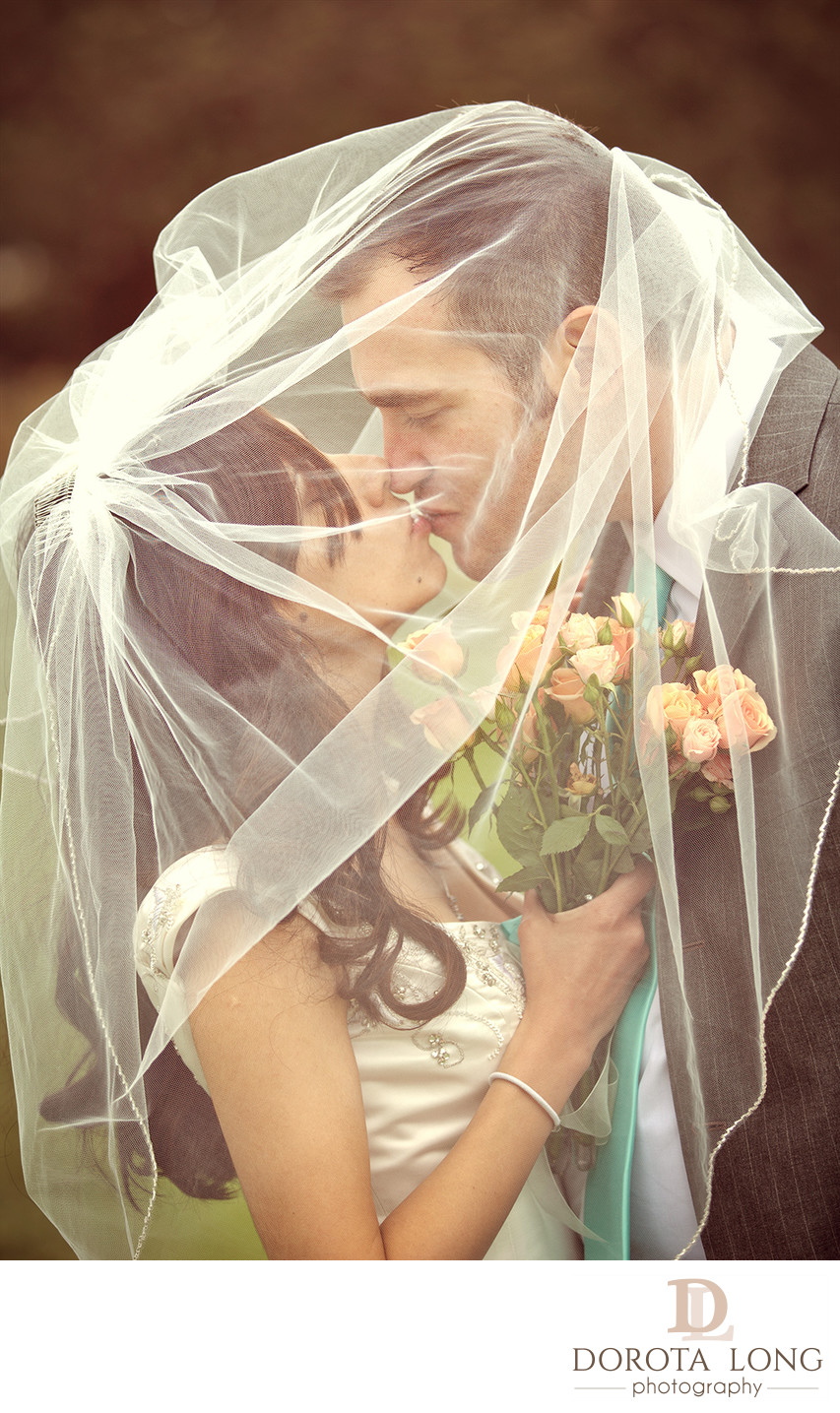 wedding couple kissing under veil in new milford, ct