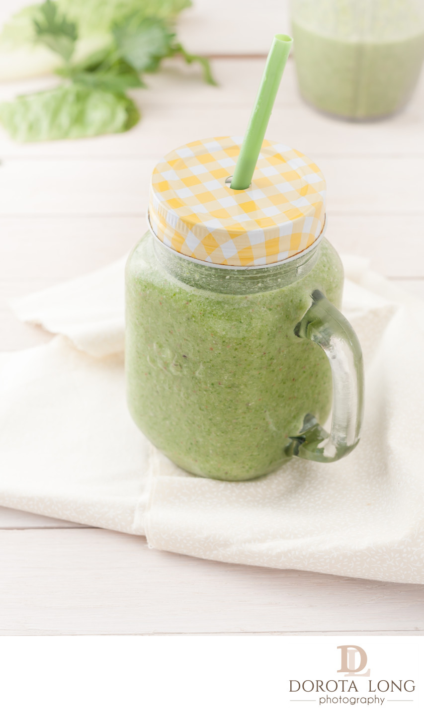 green smoothie in a glass jar with lid and a straw