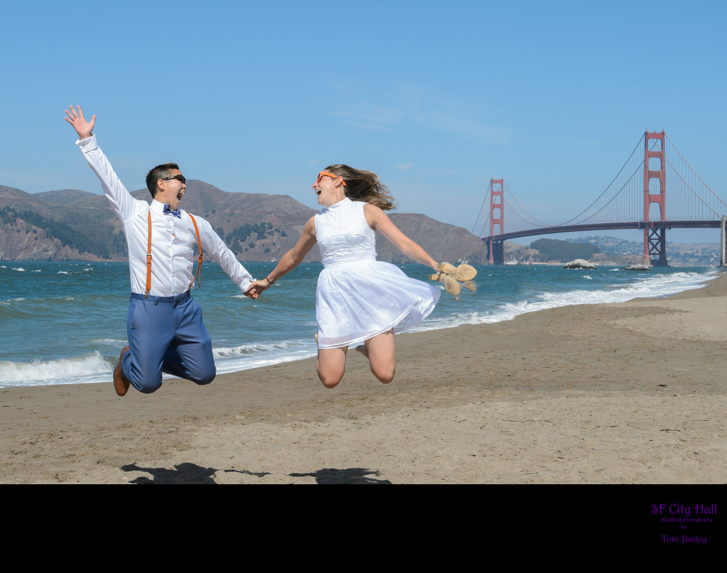 A LGBTQ  Couple jumping at Baker Beach with the Golden Gate Bridge