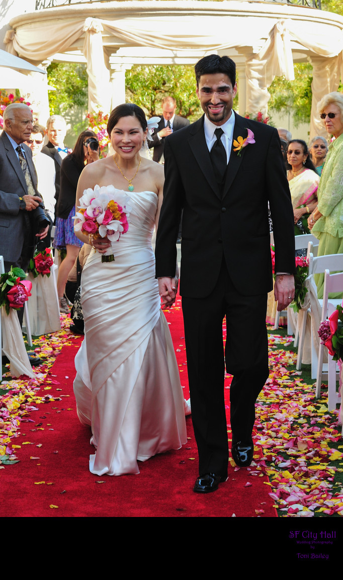 bride and groom walking down flower aisle