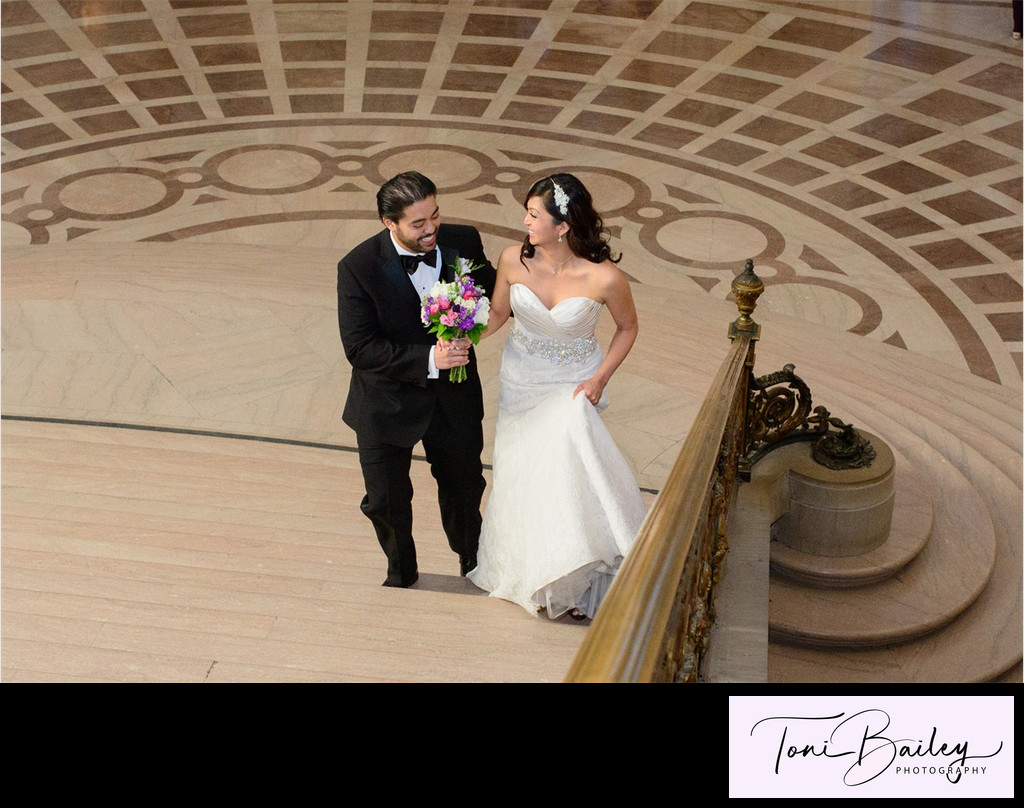 beautiful couple walking up the grand staircase