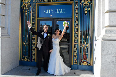 newlyweds at city hall door sign