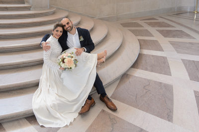 Happy couple sitting on staircase in San Francisco