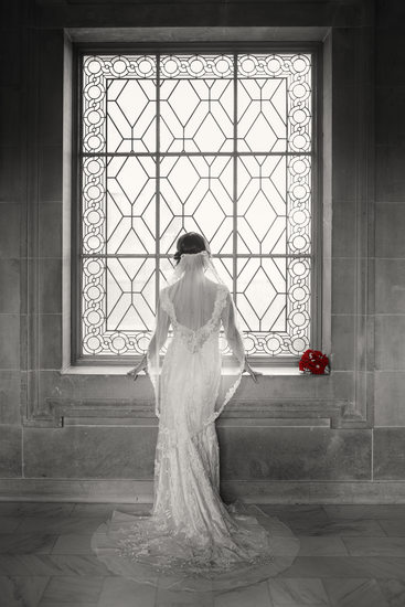 Bride with red roses in window