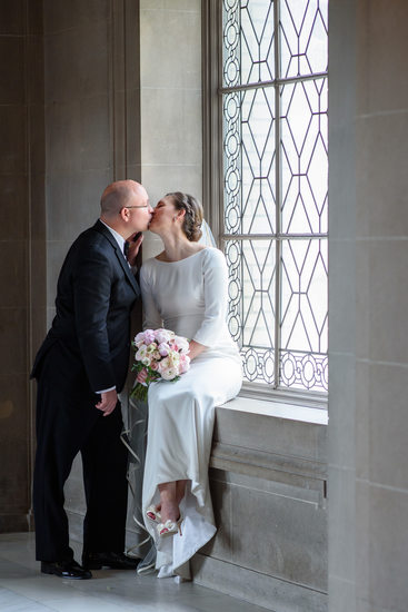 bride and groom kissing in window light at third floor window