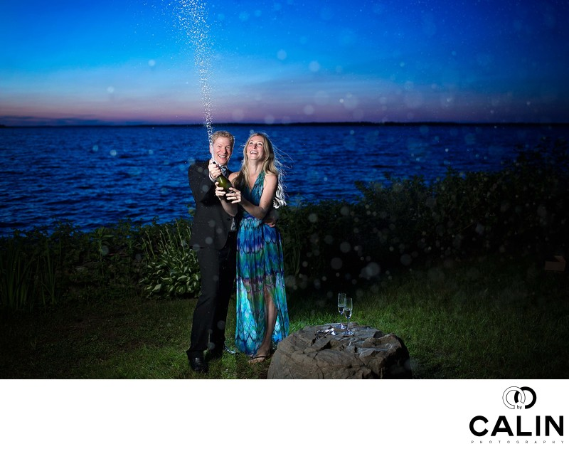 Engagement Photo of Couple Popping Champagne Bottle