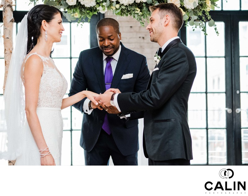 Groom Places Ring on Bride's Hand at Storys Building Wedding
