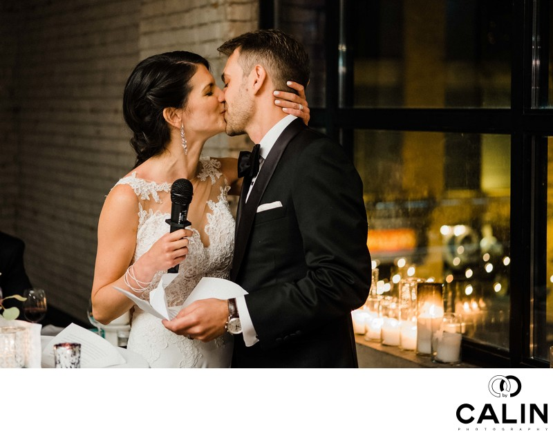 Bride and Groom Kiss During Speech at Storys Building Wedding