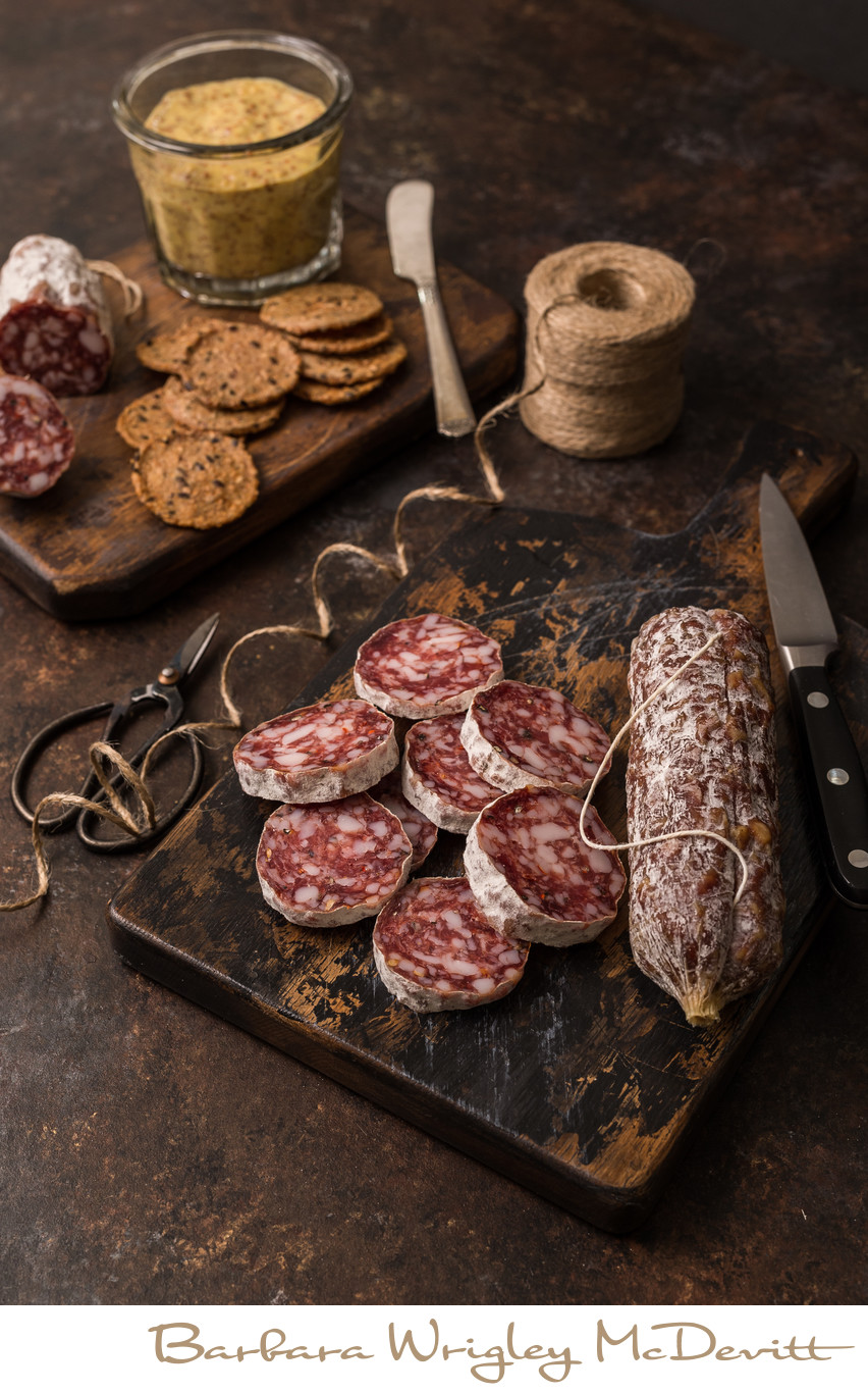 Array of spicy salami slices with hot mustard and crackers