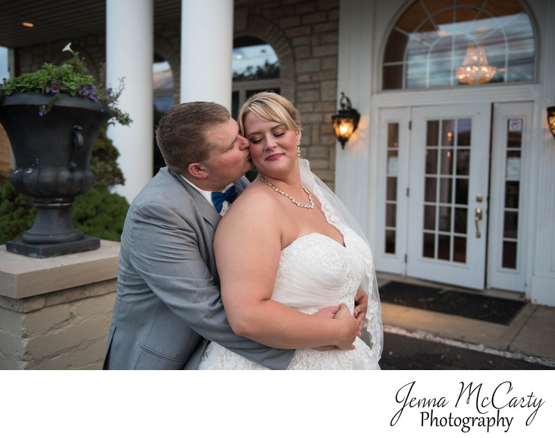Groom kissing Bride in front of Reception in Massillon