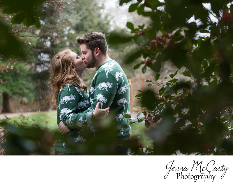 Engaged Couple Kissing through Holly Berries in Ohio