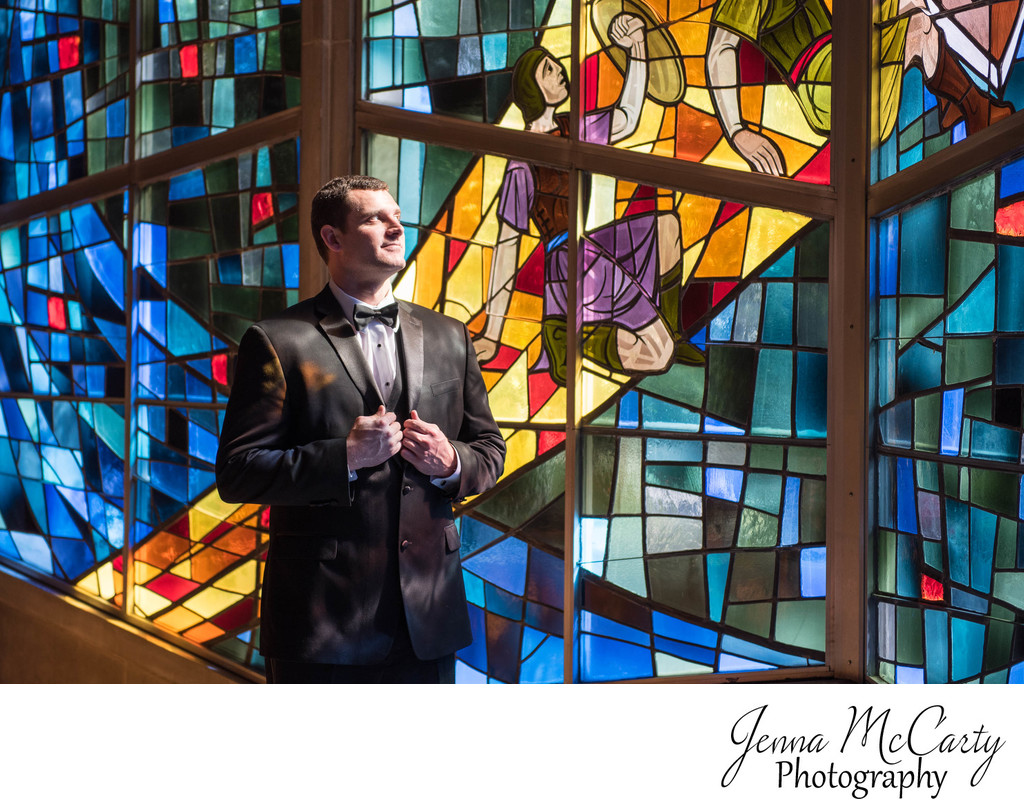 Groom standing by Stained Glass in Youngstown Ohio