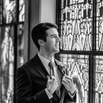 Groom looking out window at St Raphael's in Bay Village