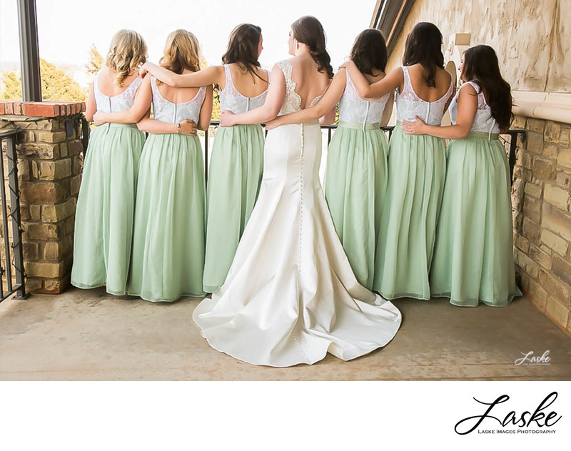 Bride and Bridesmaids Wrap their Arms Around Each Other Back View