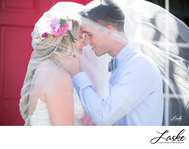 Groom Under Veil Leans In To Kiss Bride