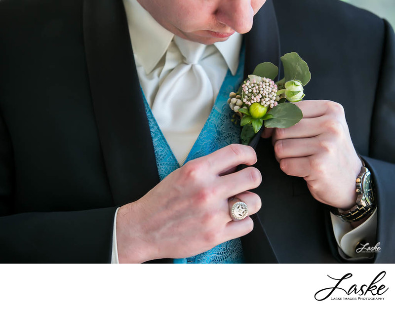 Groom Pins His Boutineer to His Tuxedo Lapel