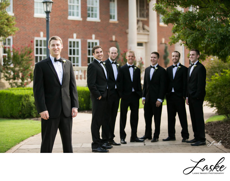Groom Poses for a Shot With Groomsmen Outside Dominion House in Guthrie, OK