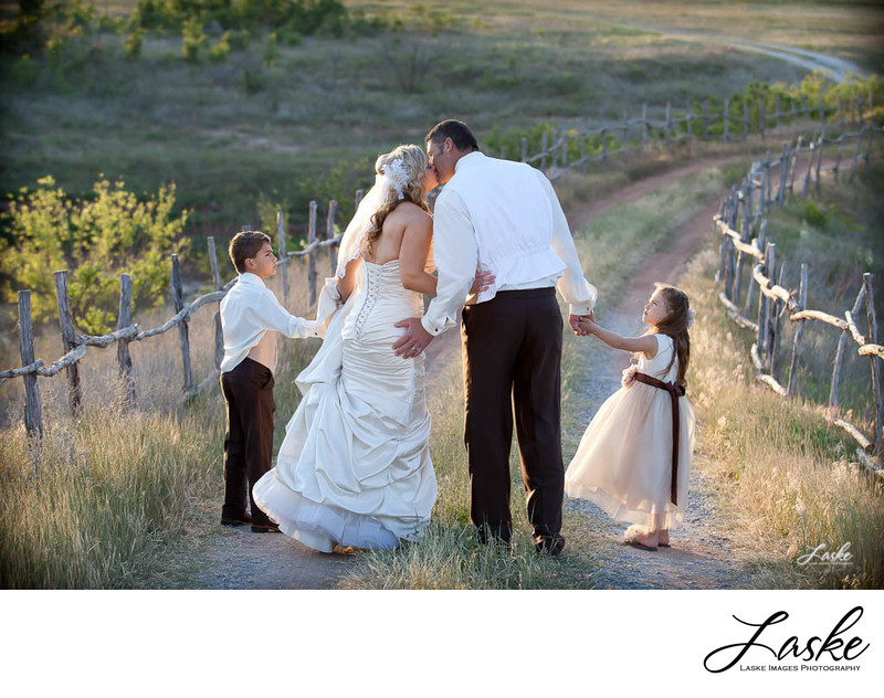 Bride and Groom Kiss with Kids Walking Down Road