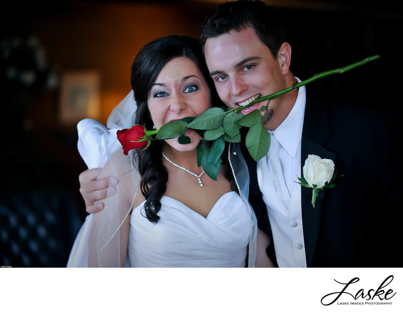 Bride and Groom hold Rose in thier Mouths