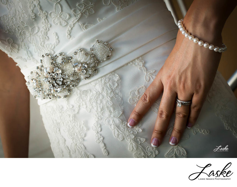 Bride rests her hand on her hip, showing off her ring and the embellishments of her dress around the waist