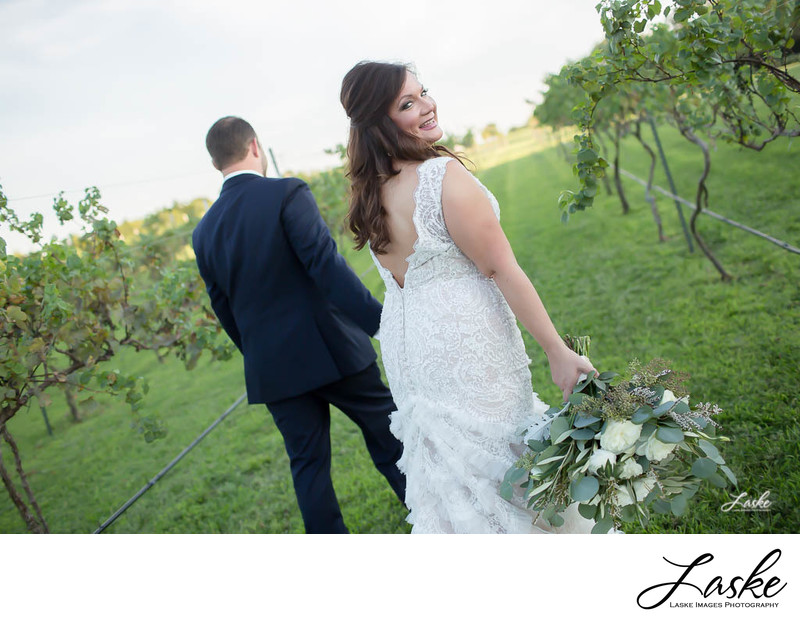 Bride Looks Back Over Shoulder as She Walks with Groom through Vineyard
