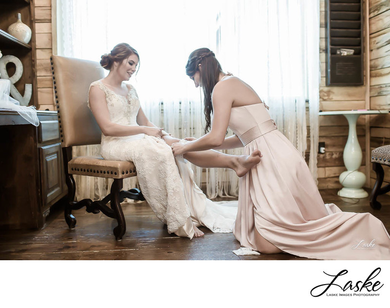 Bridesmaid helps Bride put on Garter as they get ready for wedding day