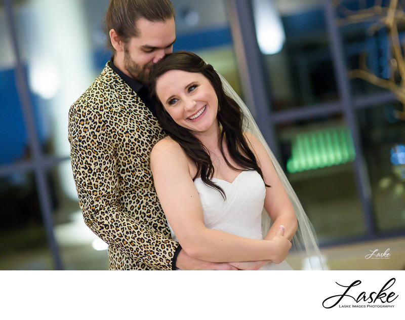 Groom in leopard print jacket stands behind Bride and wraps his arms around her