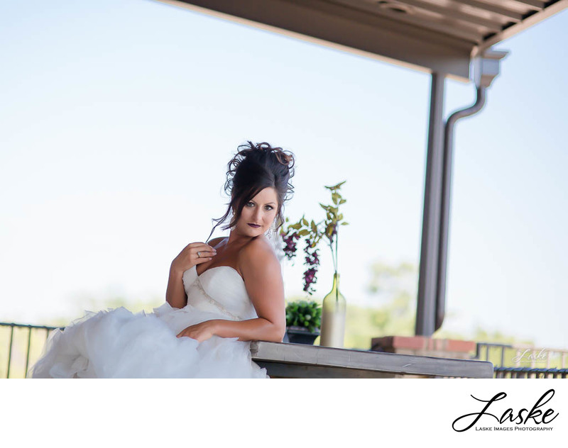 Bride Sits at Table with Flowers Outside