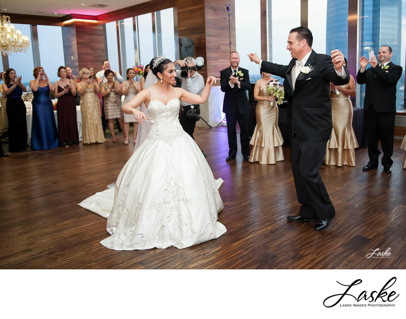 Bride and Groom dancing at their wedding reception as the guests stand around them clapping to the music.