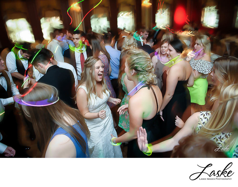 Bride Laughs as She Dances at Wedding Reception in Crowd of Guests Waving Glow in the Dark Necklaces