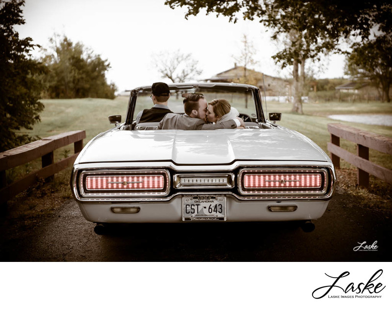 Couple sits in backseat of old thunderbird kissing.