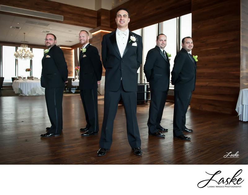Groom Stands Straight On Groomsmen Facing Away From Each Other
