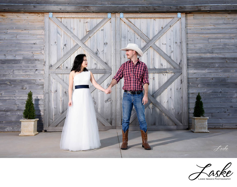 Groom holds his bride's hand while they stand outside barn