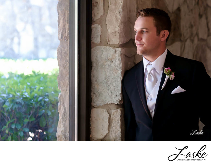 Groom in his Tux leans against Wall and Looks out Window