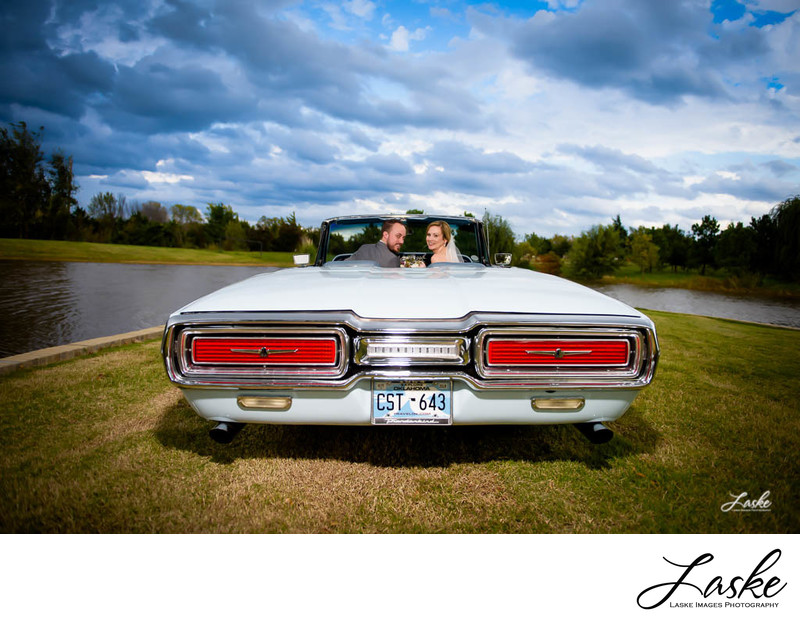 OKC Wedding Photographers Couple sits in an old car by the lake on their wedding day
