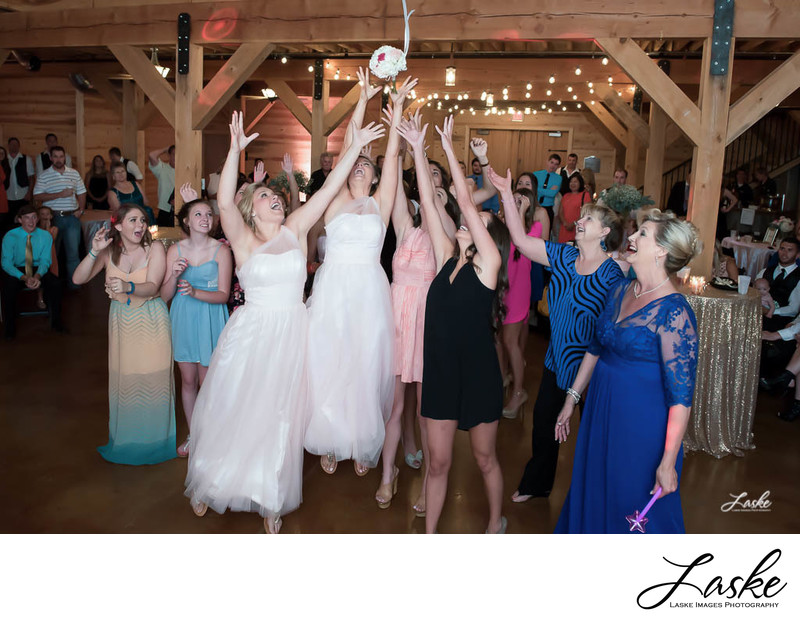Single Ladies Reach Up to Catch Bouquet During Toss at Wedding Reception