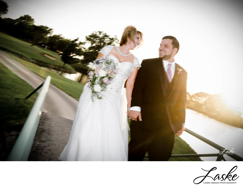 Bride and Groom laugh as they walk across the bridge at Oak Tree Country Club in Oklahoma City, Oklahoma.