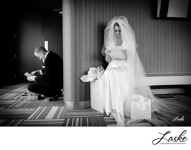 Bride and Groom Sit around the corner From each other reading wedding day letters