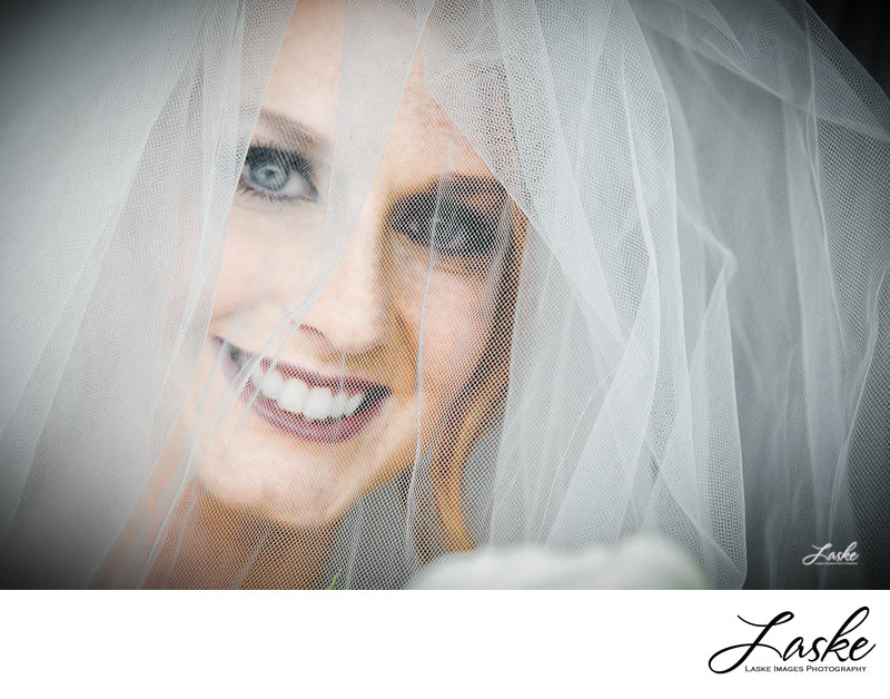 Closeup of Bride Smiling Behind Veil on Wedding Day