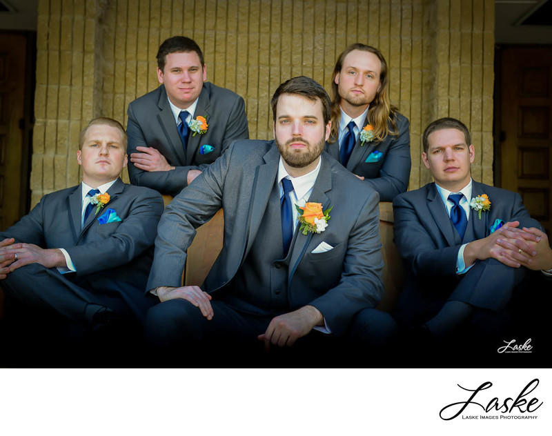 groom and groomsmen pose straight faced on wedding day
