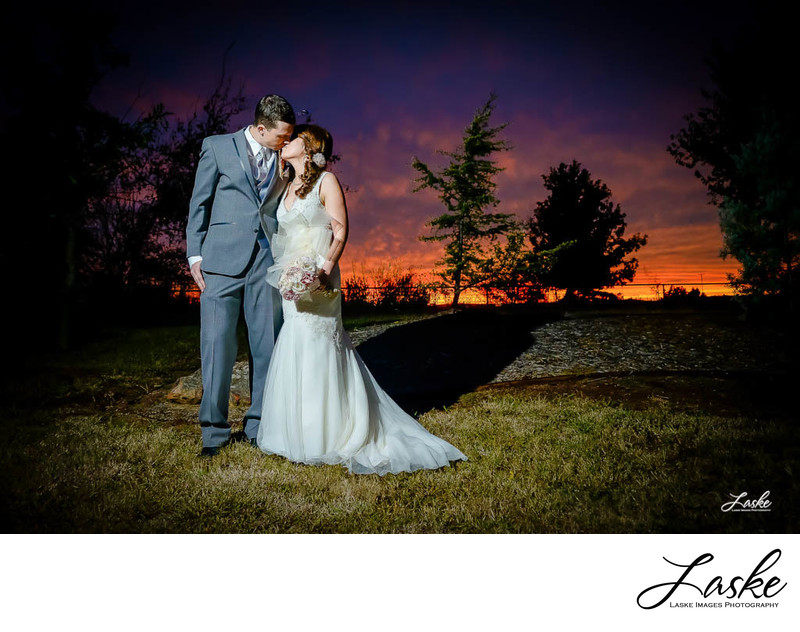 Wedding Photographers in OKC The Bride and Groom Kiss with A Beautiful Sunset Behind them over the Horizon