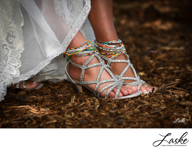 Bride's sandals and colorful ankle bracelets.