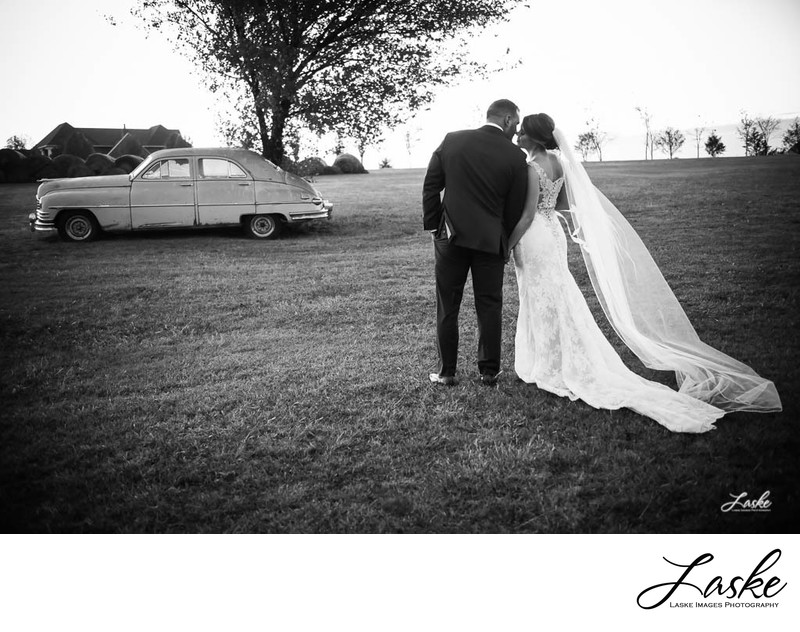 Bride and Groom Walk Across the Field to an Old Car