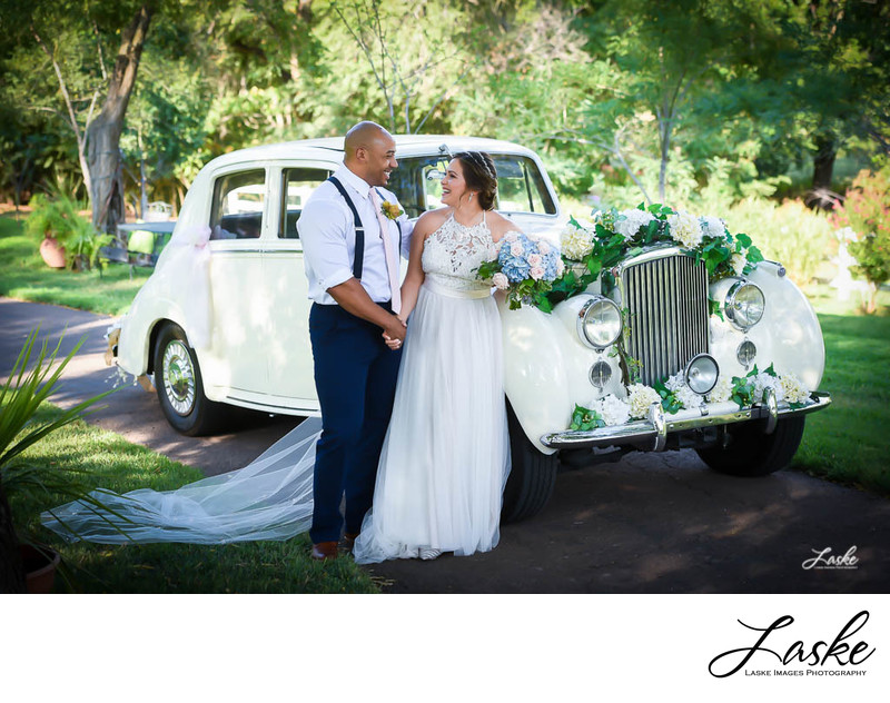 Bride and Groom Stand By Bentley Smiling on Wedding Day